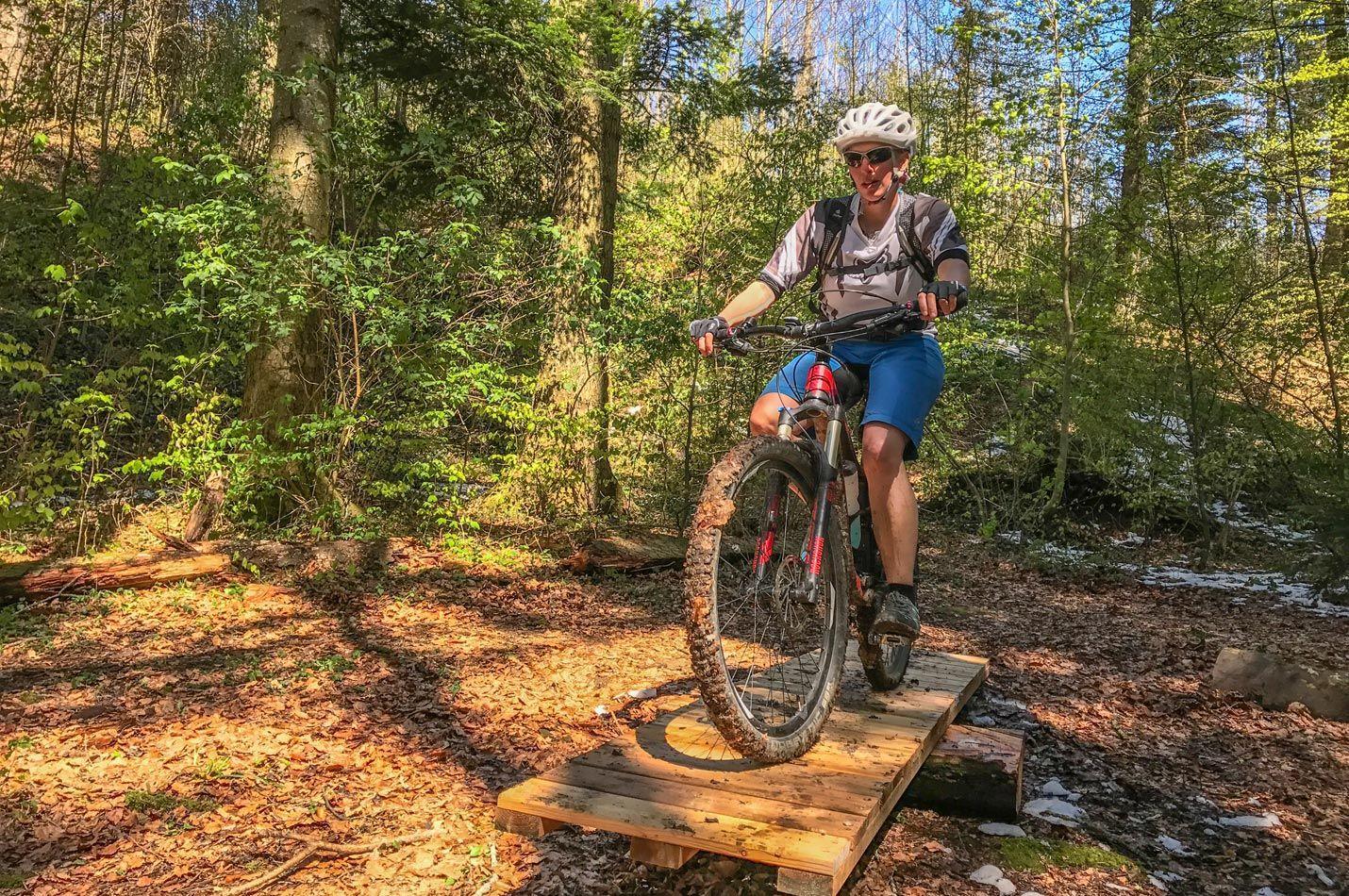 Biketechnik Kurs im Wald mit einer Bikerin auf einer Wippe