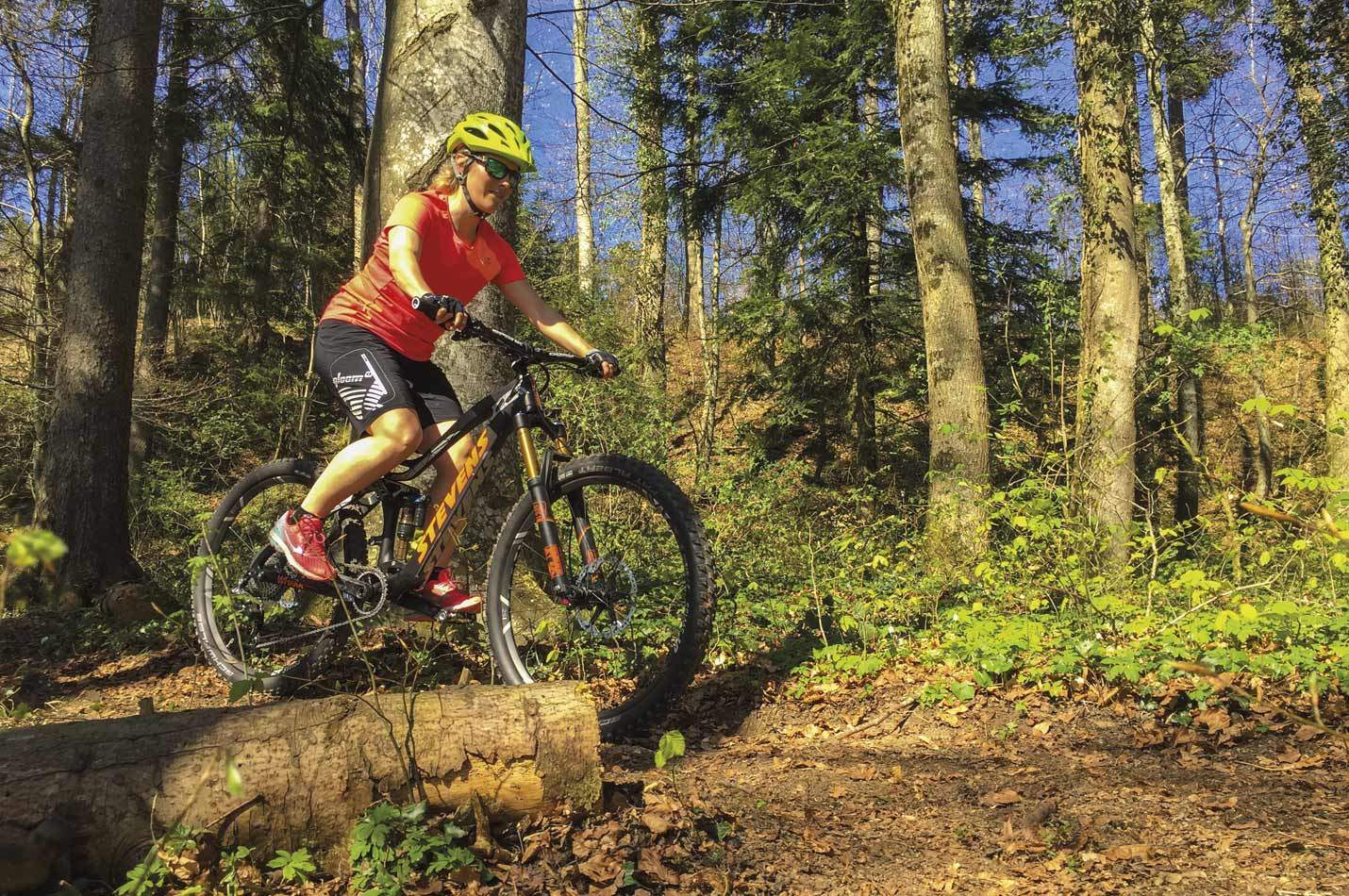 Basic Bike Kurs für Frauen mit einer Bikerin bei Abendlicht auf einem Trail im Wald