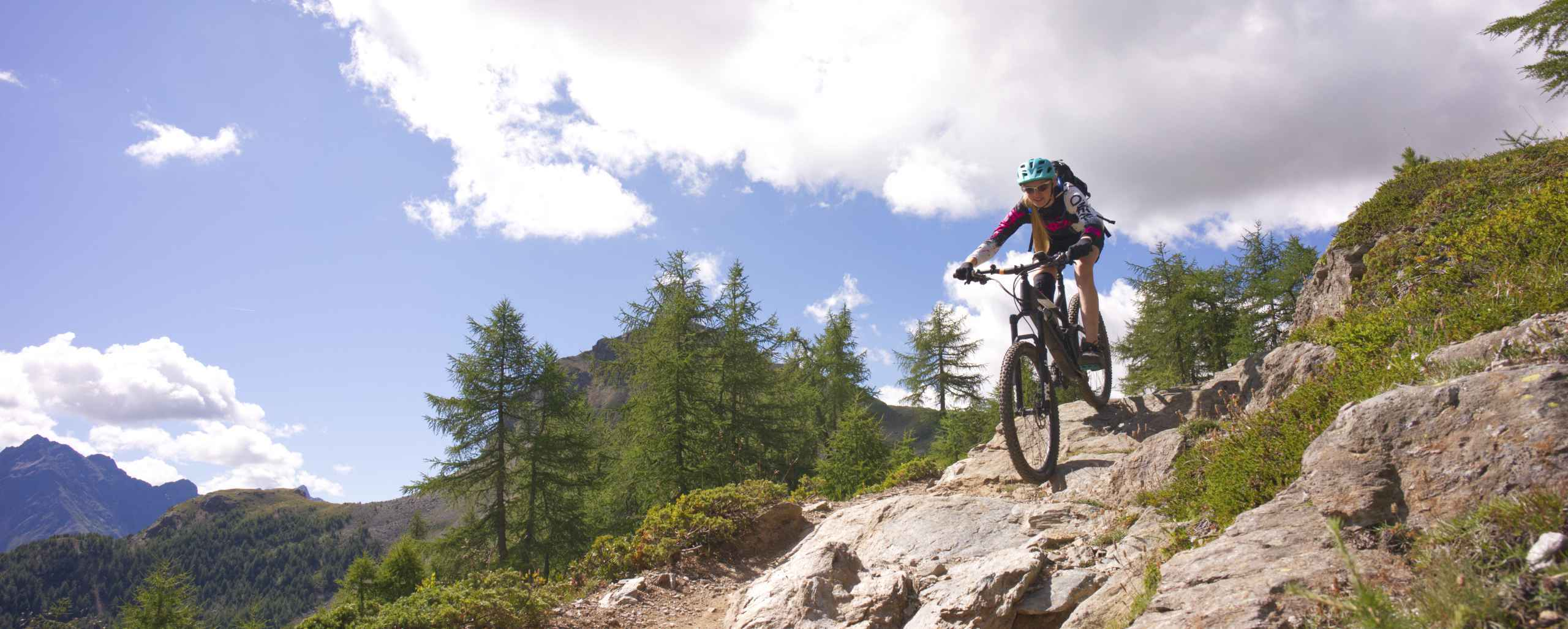 Bikerin auf Felsplatte