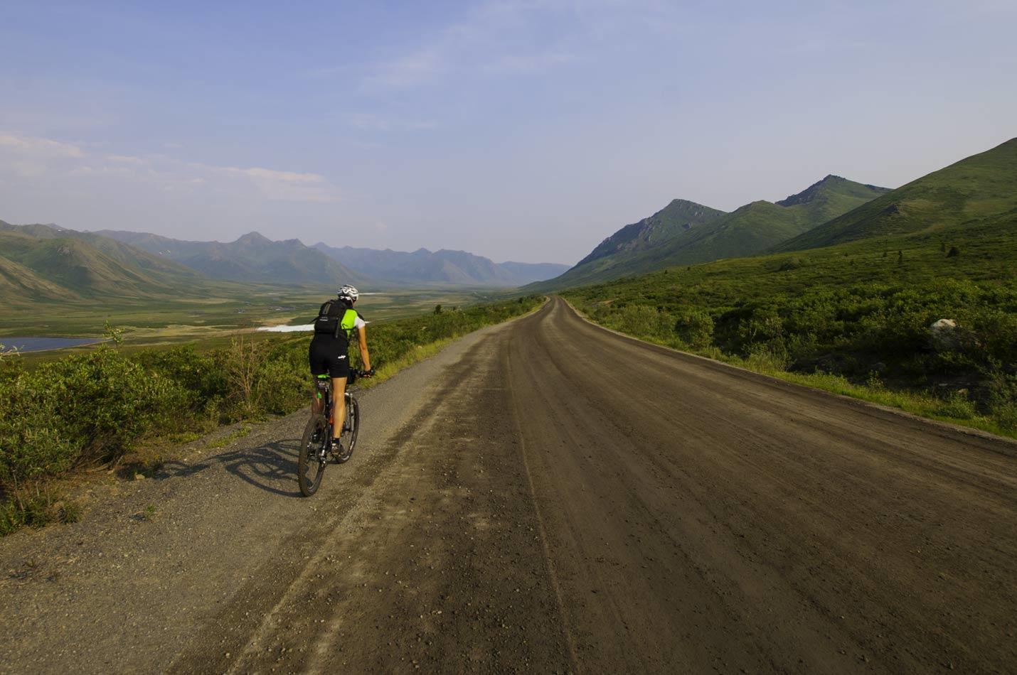 Kanada Dempster Hwy Eine Bikerin auf einer endlosen Schotterstrasse
