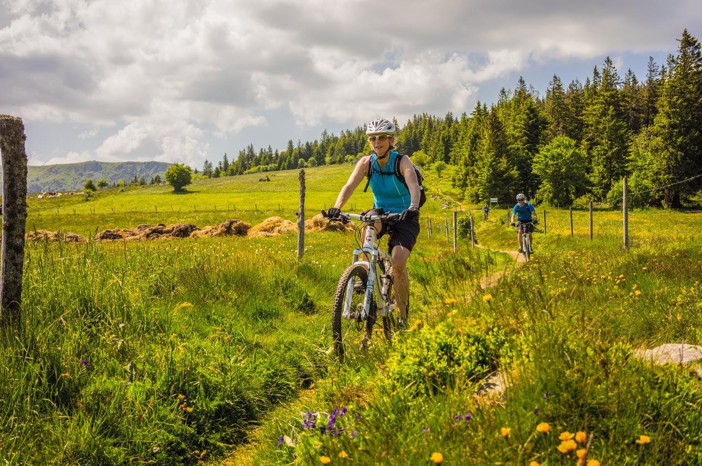 Ladies Elsass Wochenende mit einigen Bikerinnen überqueren auf einen Trail eine schöne Frühlings-Wiese