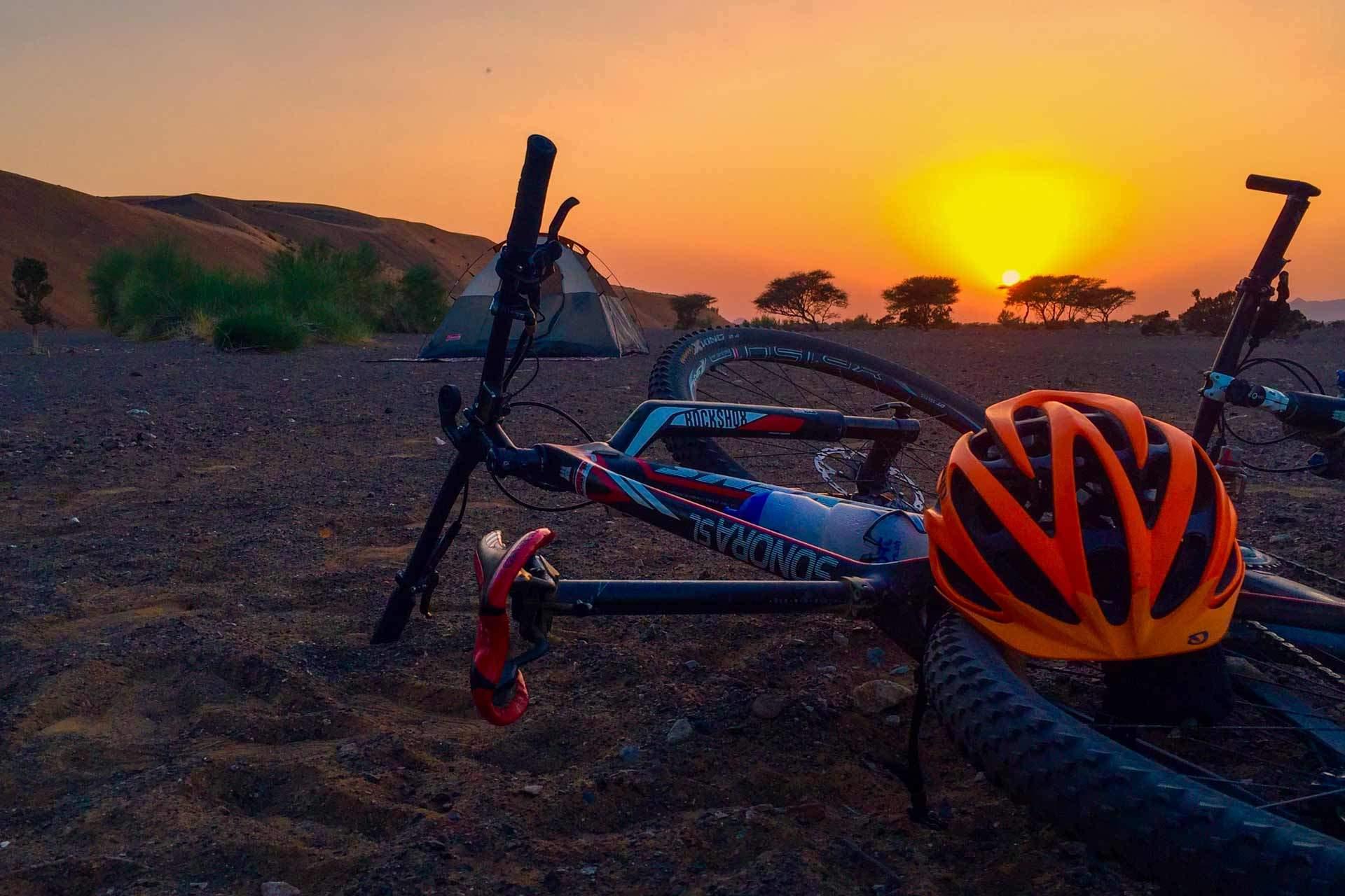 Ein Bike mit Helm und Zelt während einer Sonnenuntergangs im Oman